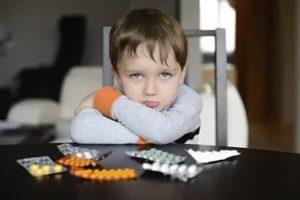 мальчик сидит за столом с таблетками