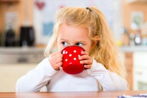 девочка пьет из кружки