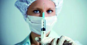 медсестра держит шприц