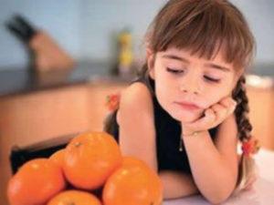 девочка смотрит на мандарины
